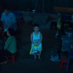 Ho- Chi- Minh city, city district, at night, kid looking up, aim-frame photography